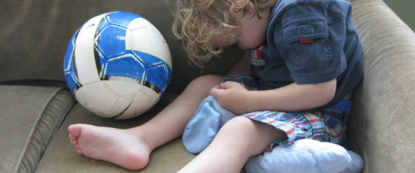 child asleep with soccer ball