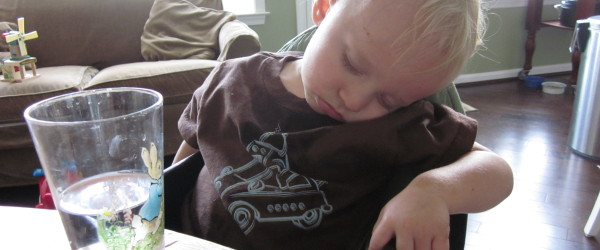 child asleep in highchair