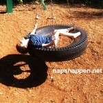 child asleep in tire swing