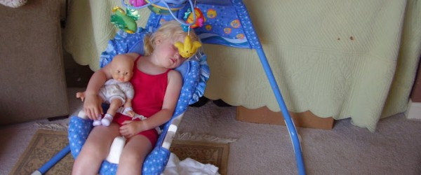 child asleep in baby swing